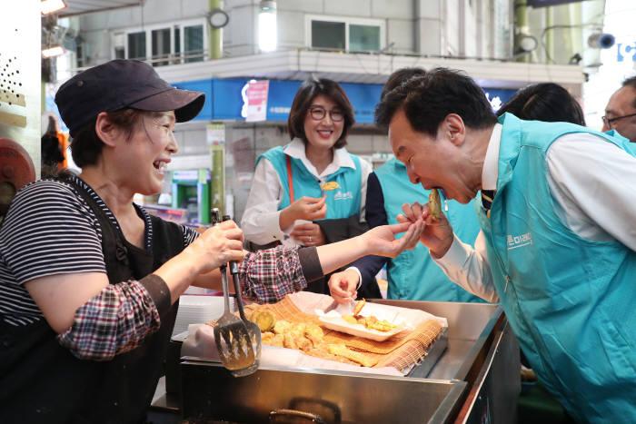 손학규 바른미래당 대표가 서울 마포 망원시장에서 상인이 건네주는 튀김을 맛보고 있다.