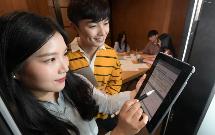 고려대학교가 정보통신기술(ICT)과 사물인터넷(IoT)을 기반으로 스마트캠퍼스를 구현한다. 모바일 신분증을 이용해 수업이 없는 빈 강의실을 스터디룸으로 사용할 수 있으며, 이용현황을 마일리지화 해 금융서비스와 연결할 계획이다. 25일 서울 성북구 고려대에서 학생들이 태블릿PC로 강의실 사용현황을 살펴보고 있다. 이동근기자 foto@etnews.com