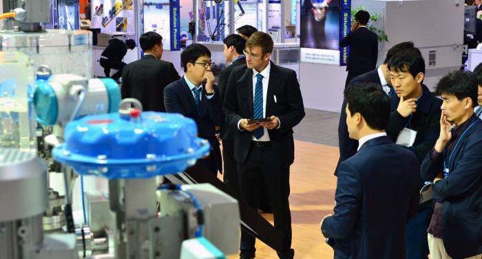 2015년 10월 경기도 일산 킨텍스에서 열린 한국산업대전 2015에서 관람객이 지멘스의 스마트공장 시스템을 둘러보고 있다. 윤성혁기자 shyoon@etnews.com