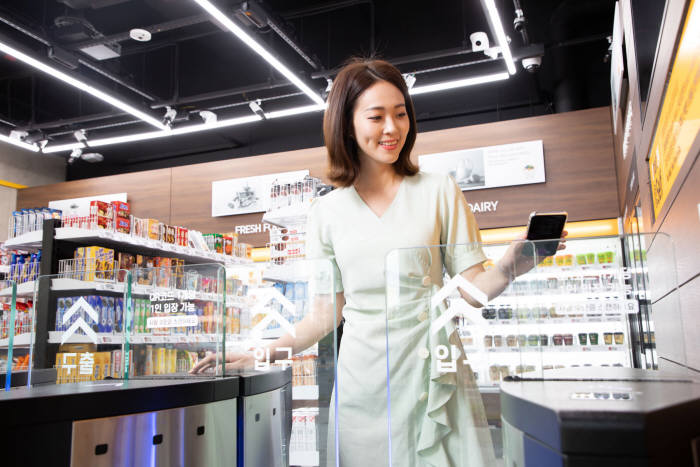신세계아이앤씨가 경기도 김포 데이터센터에 오픈한 미래형 셀프 매장을 찾은 한 고객이 QR코드를 스캔한 후 입장하고 있다.