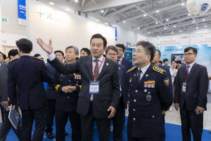 민갑룡 경찰청장(오른쪽 두 번째)이 쿠도커뮤니케이션 부스를 방문해 김용식 대표(오른쪽 세 번째)로부터 도심에서 진행되는 대규모 집회를 안전하게 진행할 수 있도록 지원하는 집회 모니터링 솔루션 세부 설명을 들었다.