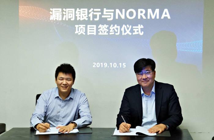 정현철 노르마 대표(오른쪽)와 뤄칭란 버그뱅크 대표가 IoT케어 수출계약서에 서명하고 있다.