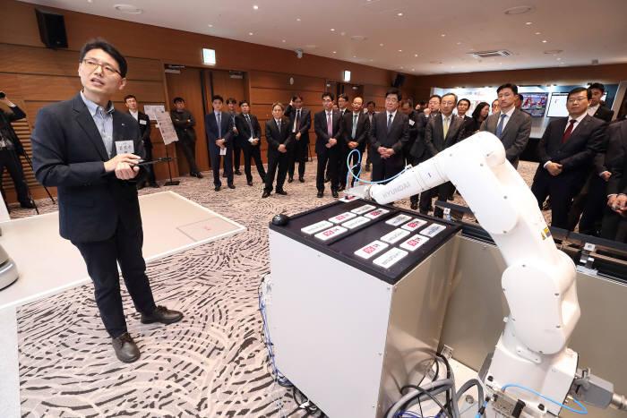 양사 임원이 AI음성인식 협동로봇 시연을 보고 있다.