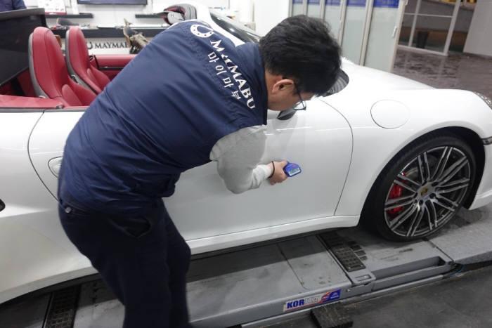 마이마부 담당자가 마이마부 스튜디오에서 중고차를 점검하고 있다.