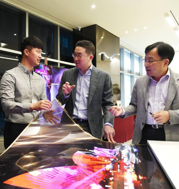 [참고사진] 구광모 (주)LG 회장이 LG사이언스파크를 방문해 윤수영 LG디스플레이 연구소장(오른쪽)과 담당 연구원과 함께 투명 플렉시블 OLED를 살펴보고 있다.