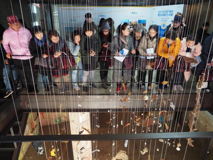 16일 인천 중구 차 스튜디오에서 환우와 가족, 관계자들이 2019 아이엠 카메라 희망여행 결과전시회의 작품을 감상하고 있다.