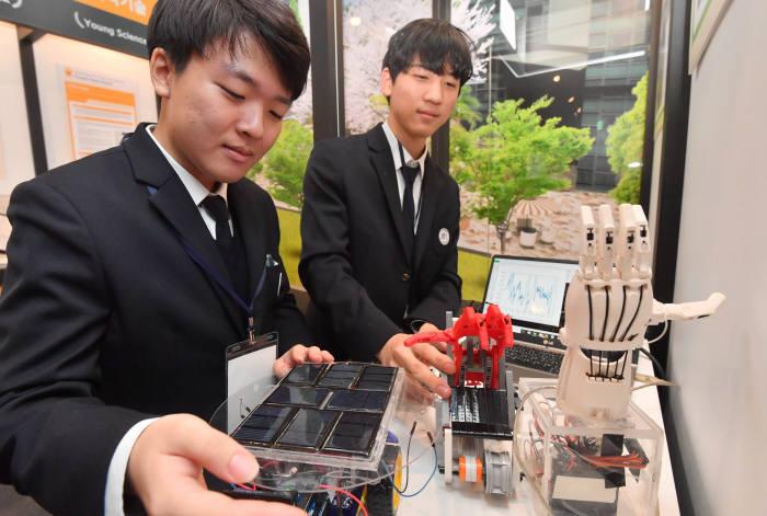 한국과학영재고 학생들이 자신이 출품한 이동형 태양광 발전기와 뇌파를 이용한 움직이는 의수를 시연하고 있다. 박지호기자 jihopress@etnews.com