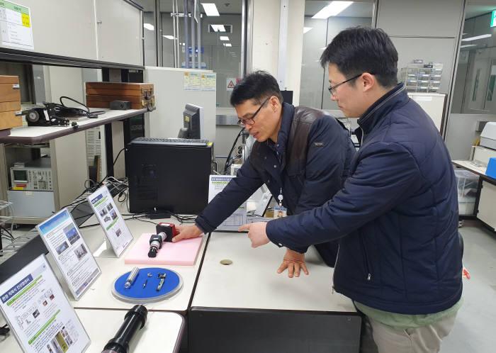 ETRI 연구진이 초분광 광학계를 두고 기술 관련 논의 하는 모습. 사진 왼쪽부터 송정호 책임연구원, 김동선 기술실무원.