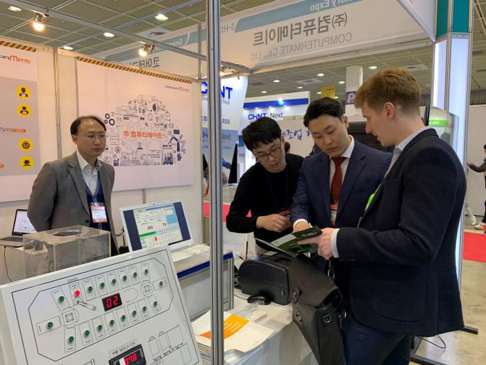 컴퓨터메이트 관계자가 최근 전시회에 참가해 해외바이어에게 관련 제품을 설명하고 있다.