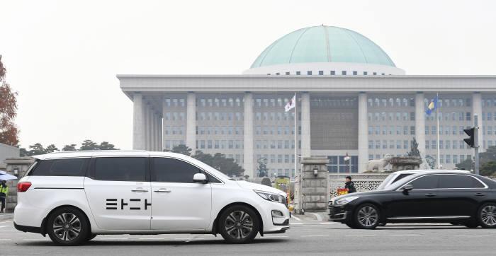 타다금지법이 지난 6일 국회 국토교통위 법안심사소위와 전체회의를 잇따라 통과하며 법사위와 본회의만을 남겨뒀다. 국회 본회의마저 통과할 경우 시행유예 기간(1년 6개월)이 끝나는 2021년 하반기부터 타다는 운행할 수 없게 된다. 9일 서울 여의도 국회 경내에서 타다 차량이 운행하고 있다. 이동근기자 foto@etnews.com