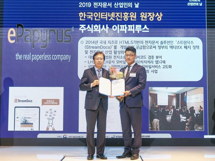 김정희 이파피루스 대표(오른쪽)가 김석환 한국인터넷진흥원장으로부터 13일 2019 전자문서 산업인의 날 유공포상을 받고 있다.