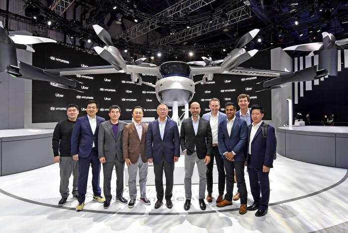 7일(현지시각) 개막한 CES 2020 현대차 전시관 내 실물 크기의 개인용 비행체(PAV) 콘셉트 S-A1 앞에서 정의선 현대차그룹 수석부회장(왼쪽 다선번째)과 다라 코스로샤히(Dara Khosrowshahi) 우버 CEO(왼쪽 여섯번째) 등 두 회사 관계자들이 기념촬영을 하고 있다.