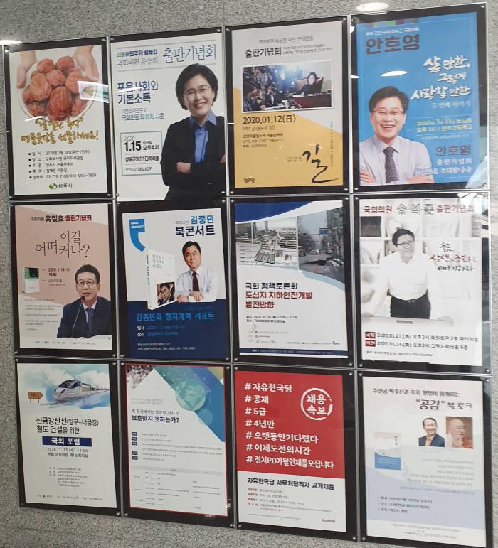 국회의원회관 한 쪽 벽면에 붙은 출판기념회 포스터들