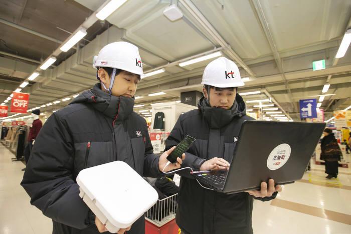 KT 네트워크부문 직원이 경기도 안양시 홈플러스 매장에서 고성능 광중계기를 설치하고 5G 서비스 품질을 확인하고 있다.