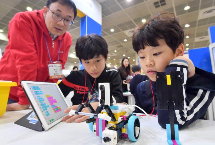 레고 스쿨프로그램에 참여한 학생들이 로봇을 조종하는 프로그램을 짜고 있다.