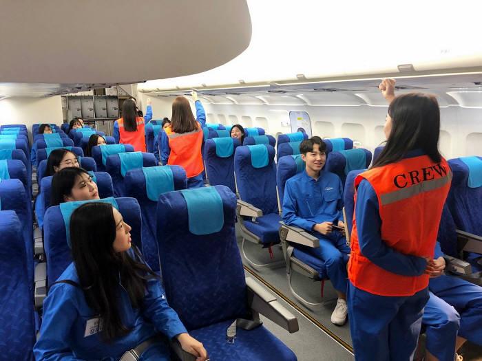 에어부산이 항공업계 진로를 희망하는 부산지역 고교생을 대상으로 꿈담기 드림 교실을 진행했다. 학생들이 에어부산 훈련복을 입고 모의 항공기 훈련장(MOCK-UP)에서 안전 교육을 받고 있다.