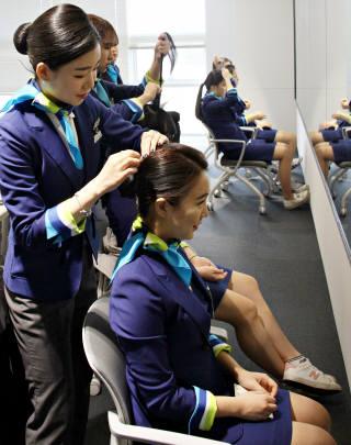 에어부산이 항공업계 진로를 희망하는 부산지역 고교생을 대상으로 꿈담기 드림 교실을 진행했다. 학생들이 에어부산 유니폼을 입고 교관에게 승무원 머리 손질법을 배우고 있다.