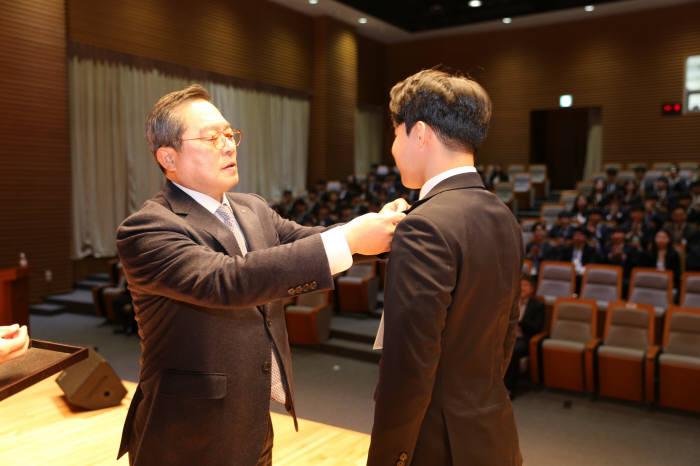 구자열 LS그룹 회장이 신입사원에서 배지를 달아주고 있다.