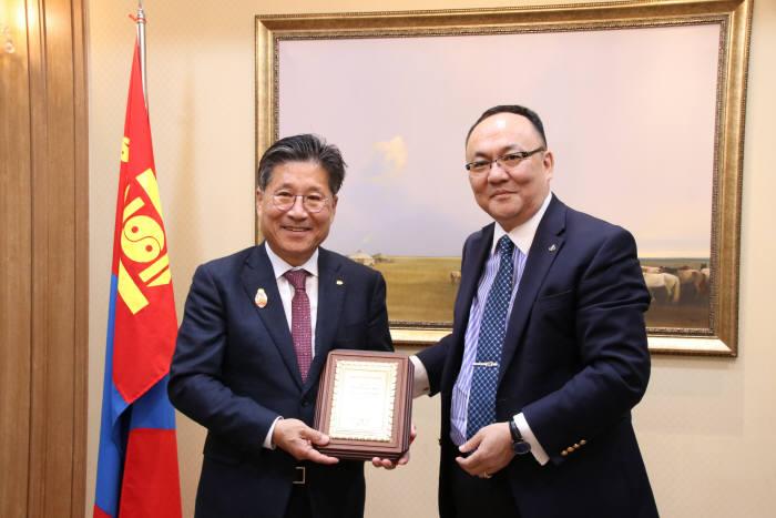 류재선 한국전기공사협회 회장(왼쪽)이 28일 에르덴투야(Erdentuya) 주한 몽골대사로부터 몽골정부가 수여하는 표창패를 받고 기념촬영했다.