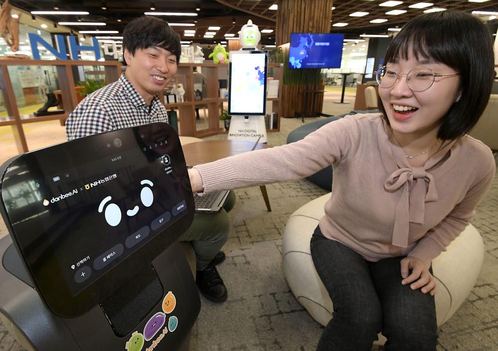 디지털 기술 내재화의 일환으로 농협은행은 안면인식 기술을 탑재한 인공지능(AI) 자율주행 로봇으로 안내, 상담 등을 수행하는 미래형 점포를 만든다. 18일 서울 서초구 NH디지털혁신캠퍼스에서 챗봇 개발업체 단비AI와 농협 관계자가 AI 자율주행 로봇을 살펴보고 있다. 이동근기자 foto@etnews.com