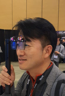 김보은 라온텍 대표가 이달 초 열린 미국 포토닉스 웨스트 전시회에서 AR글라스 시제품을 살펴보고 있다. <사진= 라온텍>