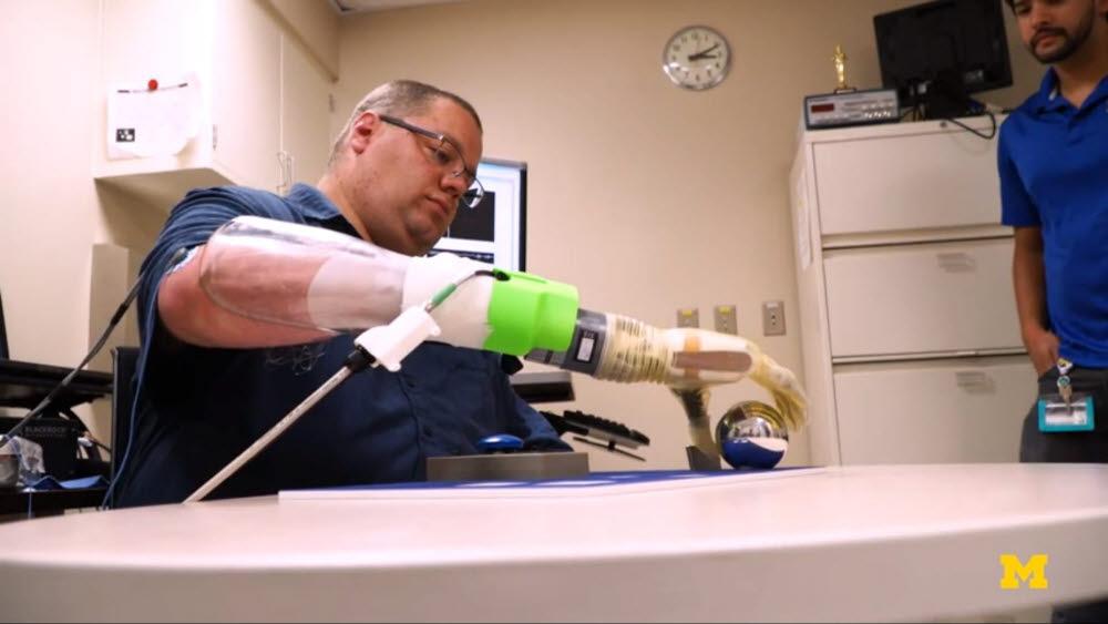 미국 미시간대 연구진이 개발한 의수를 장착한 환자가 금속 공을 집어올리고 있다. <사진=미시건대학교 영상 갈무리>