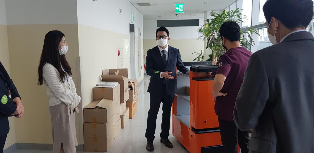 천영석 대표(사진 가운데)가 지난 12일 서울의료원 관계자들을 대상으로 자율주행 카트 따르고 사용방법을 소개하고 있다. 사진출처=트위니