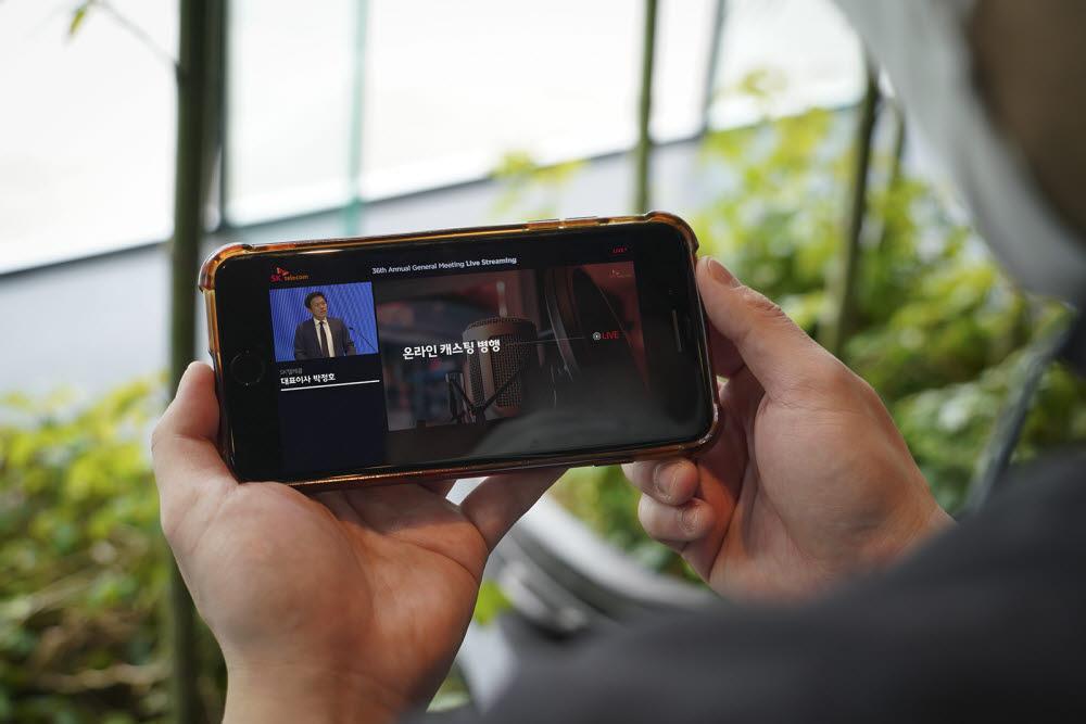 SK텔레콤 주주가 26일 스마트폰으로 SK텔레콤 온라인주주총회를 시청하고 있다.