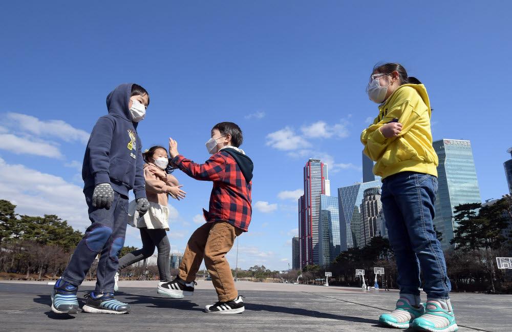 미세먼지 농도가 좋음을 보인 2월 27일. 서울 여의도광장에서 푸른 하늘 아래 마스크를 쓴 어린이들이 뛰어놀고 있다. (사진은 기사와 직접적인 연관이 없습니다) 이동근기자 foto@etnews.com