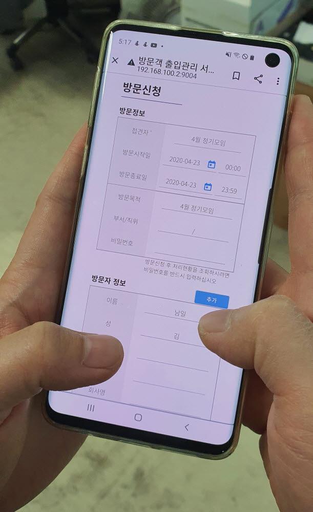 방문자가 스마트폰을 이용해 현장에 가지 않고 원격지에서 본인 바이오정보를 방문 예정지의 서버에 미리 등록하고 있다.