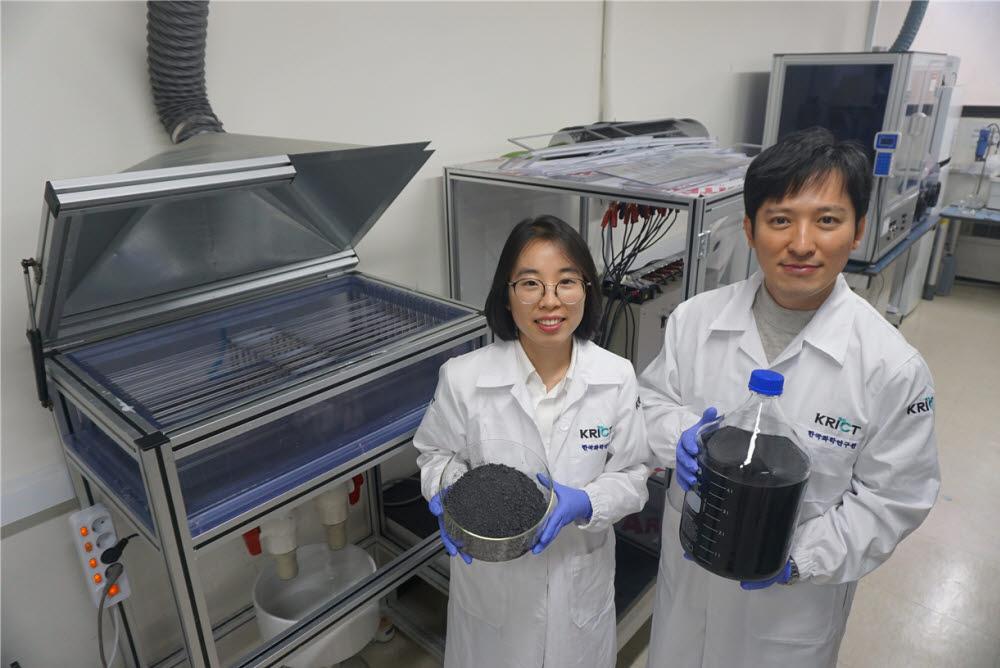 이제욱 화학연 책임연구원(사진 오른쪽)과 권연주 연구원(왼쪽)이 멀티 전극 시스템으로 생산한 그래핀 용액과 가루를 들어보이는 모습. 두 연구원 뒤에 있는 장치가 차세대 전기화학 박리공정이 적용된 멀티 전극 시스템이다.