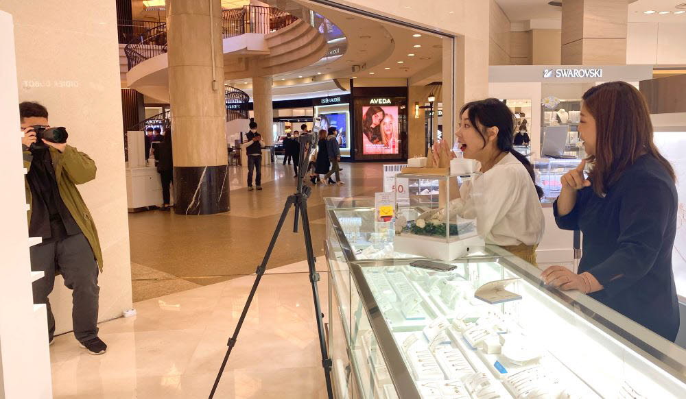 AK플라자 매장에서 직원들이 모바일 라이브 방송을 촬영하고 있다.