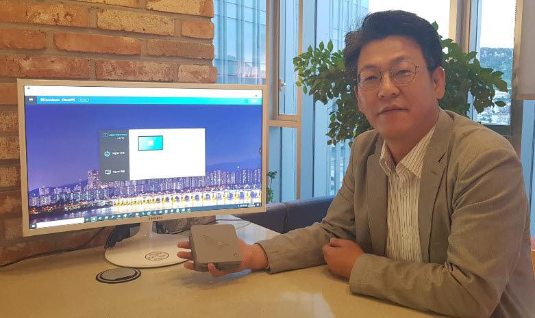 김효준 SK브로드밴드 PO가 자체 개발한 씬클라이언트를 들고 사진촬영을 하고 있다. PC 화면은 SK브로드밴드 클라우드PC 서비스 로그인 환경.