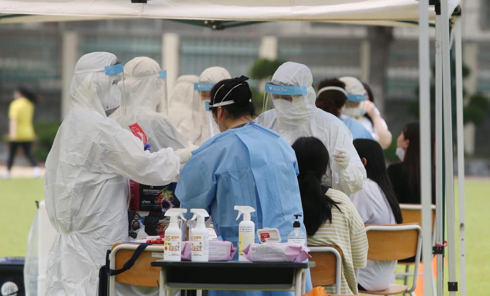6일 오전 인천시 연수구 인천뷰티예술고 운동장에 설치된 선별 진료소에서 학생들이 검체 검사를 받고 있다. 연합뉴스