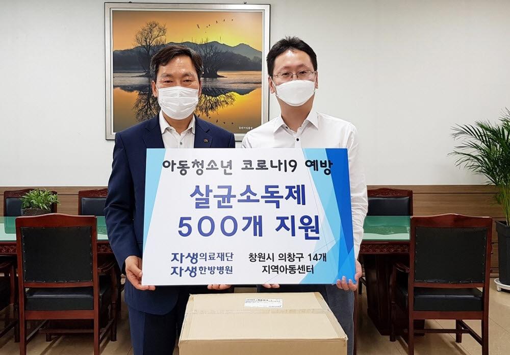 강인 창원자생한방병원 병원장(오른쪽)이 창원시 의창구청 홍명표 구청장(왼쪽)에게 손소독제 500개를 기부하고 있다. (사진=자생의료재단)