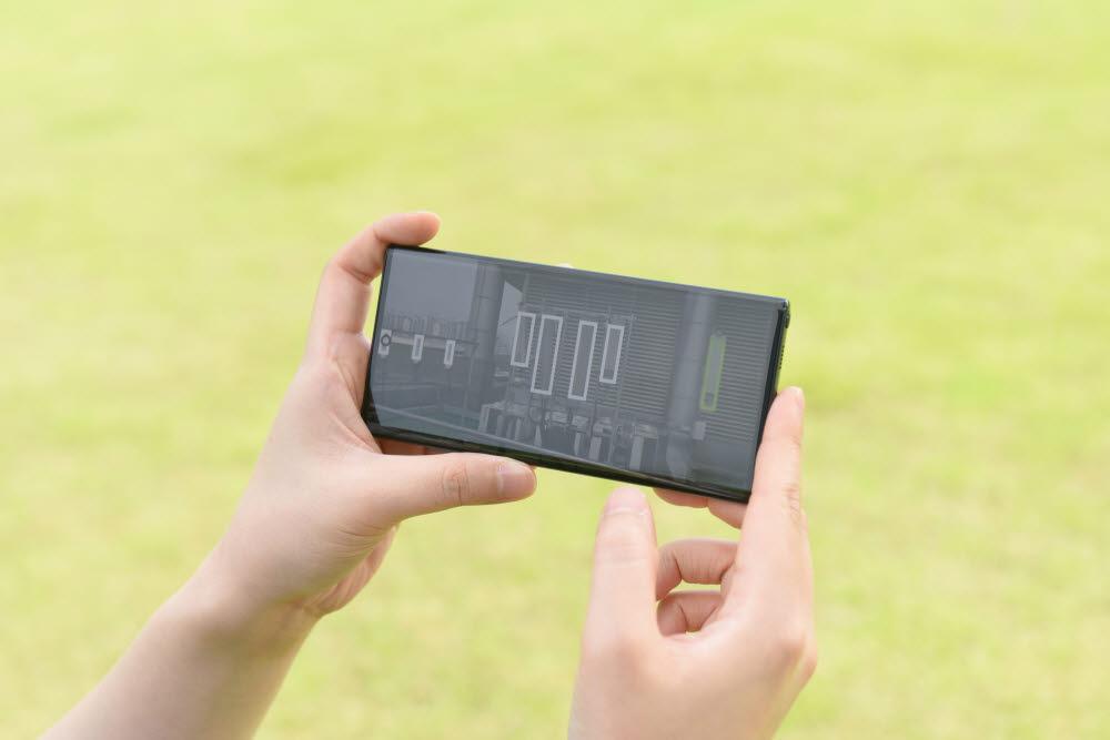 삼성 5G 네트워크 성능 최적화 솔루션을 탑재한 드론으로 촬영한 안테나와 기지국 정보를 스마트폰으로 확인하는 모습
