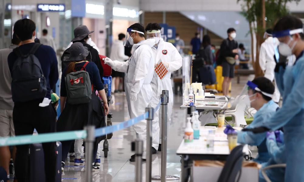 20일 오후 인천국제공항 제2여객터미널에서 네덜란드 암스테르담 등에서 온 입국자들이 방역 관계자의 안내를 받으며 입국장을 빠져나가고 있다. 연합뉴스