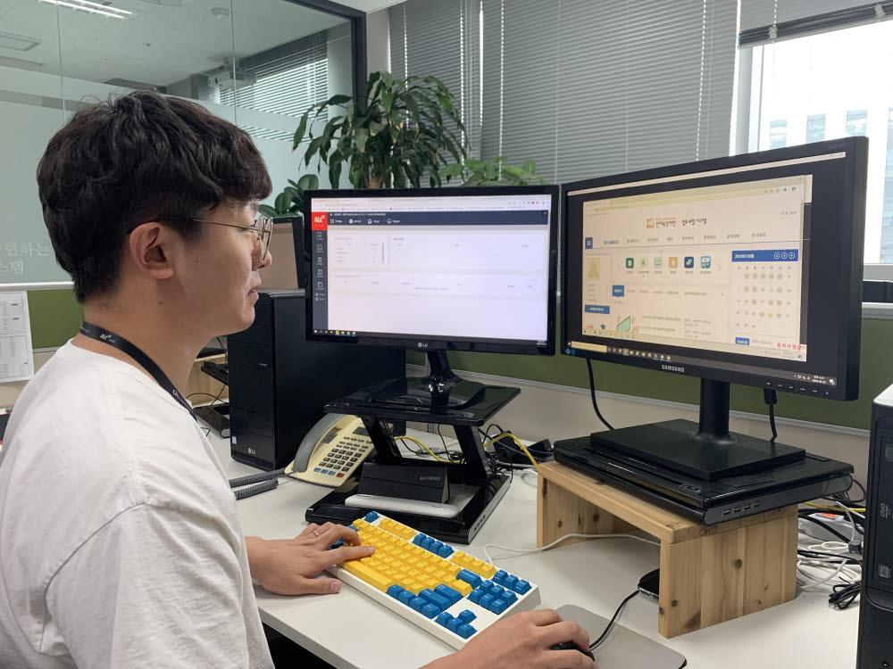 씨앤에프시스템 직원이 화성시인재육성재단이 구축한 통합경영정보시스템 화면과 올샵(ALL#) 전사자원관리(ERP) 시스템 화면을 살펴보고 있다.