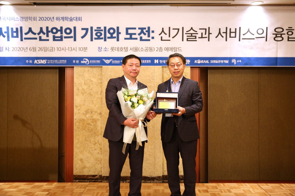 26일 서울 롯데호텔에서 열린 2020 한국서비스경영학회 하계 학술대회 서비스 엑셀런스 어워드에서 유한주 한국서비스경영학회 학회장(오른쪽)과 유덕상 아워홈 대표이사(왼쪽)가 기념촬영을 하고 있다.