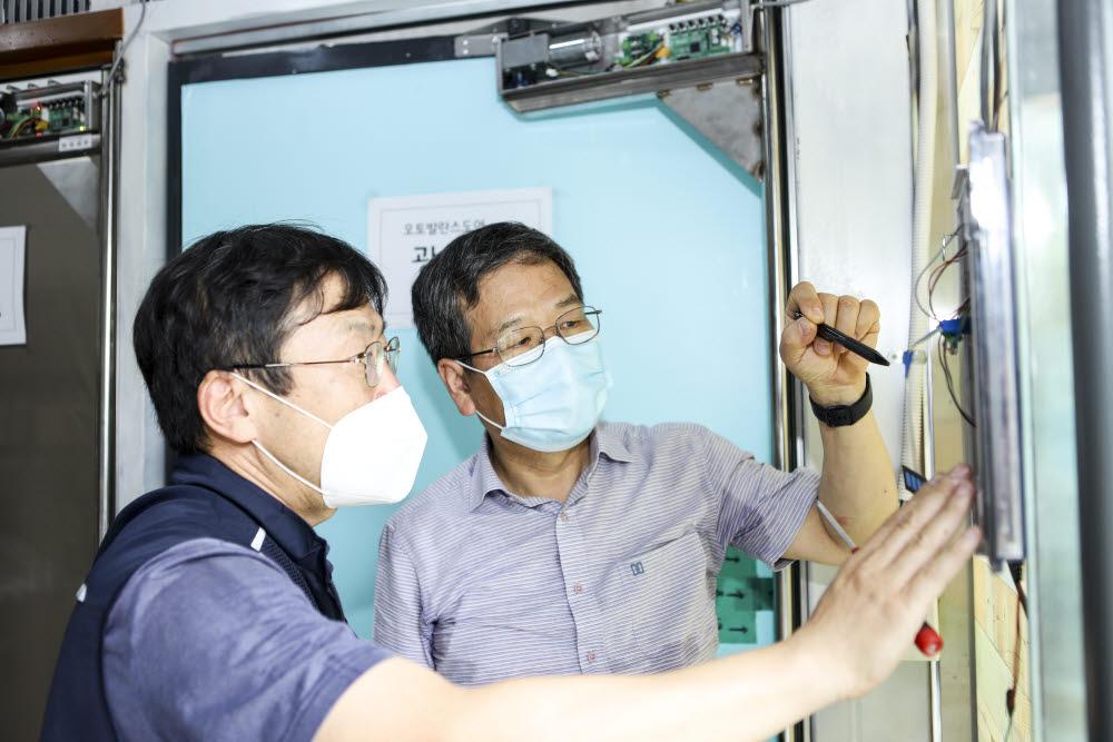 함상용 기계연 책임기술원(오른쪽)과 백진기 세이인 대표(왼쪽)가 자동문 적용 방안을 논의하고 있다.