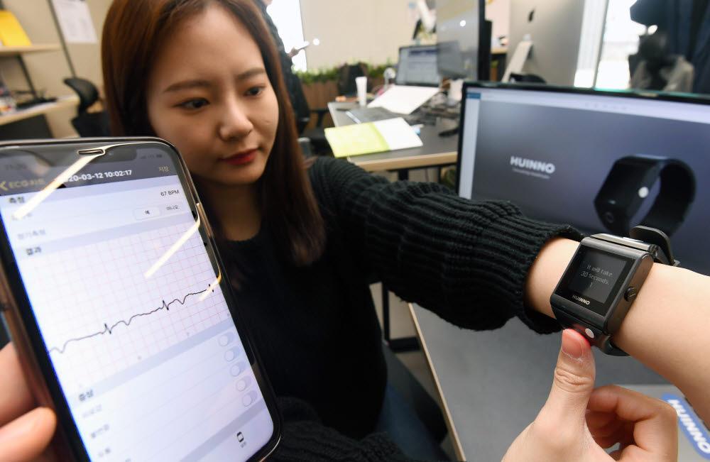 지난 3월 휴이노 관계자가 손목시계형 심전도 측정기 메모워치를 시연하는 모습. 메모워치는 ICT 규제 샌드박스 1호로 선정된 손목시계형 심전도 측정기로 맥박과 심전도, 산소 포화도 등을 측정할 수 있으며, 취합된 정보를 의료진에 전송하는 기능을 갖고 있다. 이동근기자 foto@etnews.com