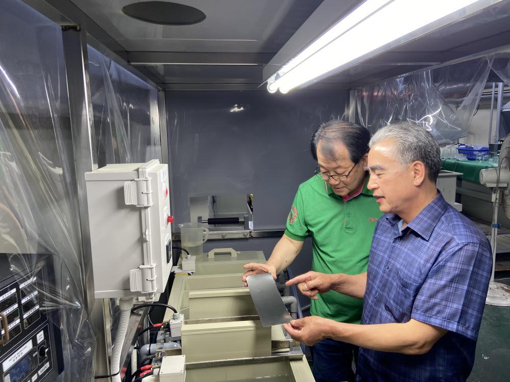 기양금속이 흑색 스테인리스 구현기술을 개발했다. 배명직 기양금속 대표(오른쪽)와 노병호 연구소장이 흑색이 구현된 스테인리스 소재를 살펴보고 있다.