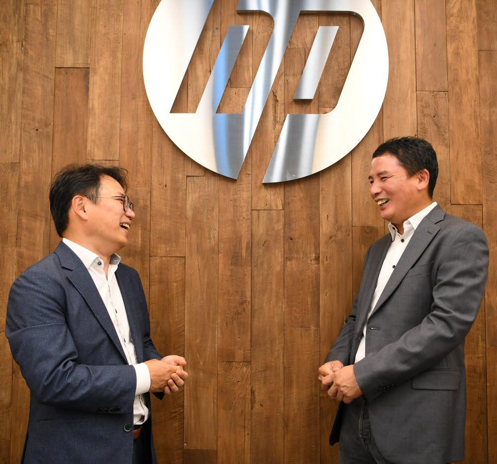 홍기범 전자신문 전자자동차부장(왼쪽)과 김광석 HP프린팅코리아 대표가 대화 중 웃음을 터뜨리고 있다.