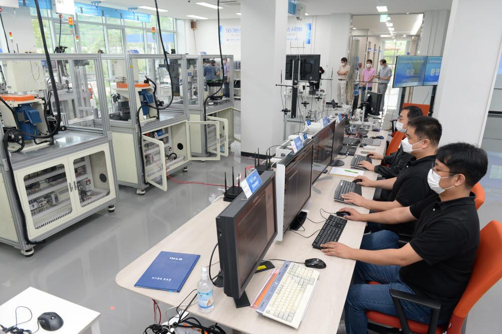 ETRI 연구진이 스마트공장 내 자동화 설비를 5G 무선 통신으로 원격으로 제어하는 모습.