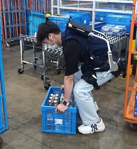 조양국제종합물류 직원이 웨어러블 슈트를 입고 물품을 나르고 있다.