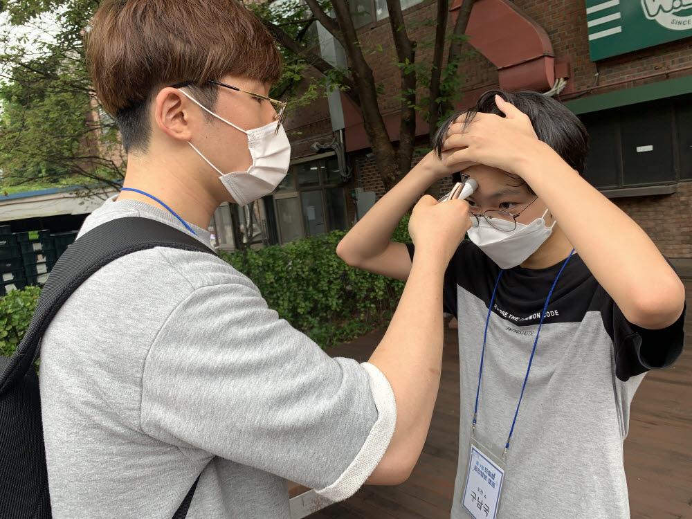 서울시립대 연구원이 드림업 공간정보 캠프 참석 학생의 발열 체크를 하고 있다.