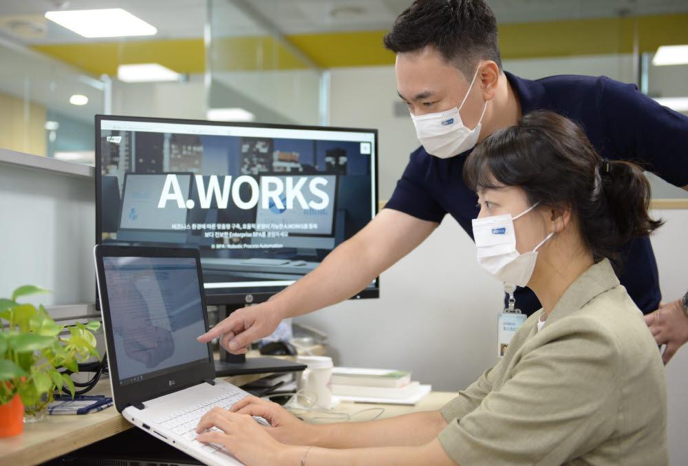 포스코ICT 직원들이 자사 RPA 솔루션인 에이웍스( A.WORKS)를 적용해 업무를 자동으로 처리한 결과를 살펴보고 있다. <포스코ICT 제공>