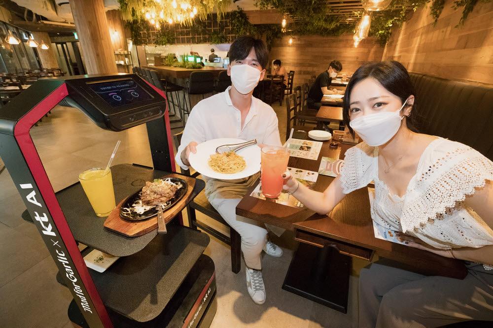 KT AI로봇이 매드포갈릭 봉은사 현대아이파크타워점에서 고객이 주문한 음식을 서빙하고 있다.