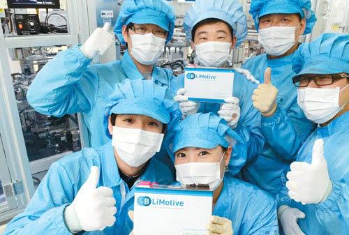 삼성SDI 울산 공장 내 전기차 배터리 생산라인 연구원들이 리튬이온 배터리 팩을 들고 엄지손가락을 치켜세우고 있다