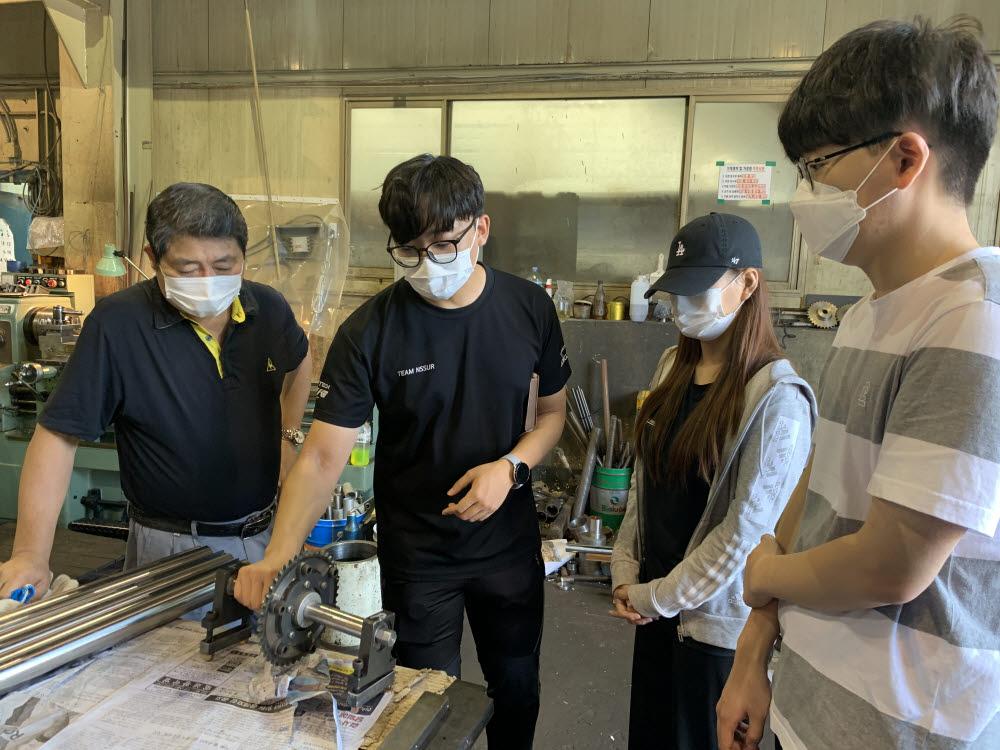 권년택 광남정밀 대표(맨 왼쪽)가 산기대 학생들과 제작한 부품을 살펴본 뒤 문제점을 자문해주고 있다.